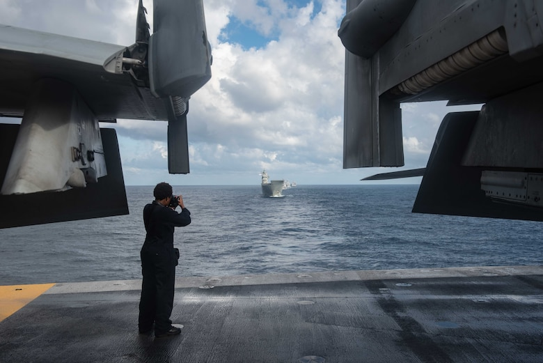 CORAL SEA (July 11, 2019) Mass Communication Specialist 2nd Class Tyra Campbell, from Philadelphia, photographs the Royal Australian Navy's HMAS Canberra (L 02), as they sail in formation during Talisman Sabre 2019 on the flight deck of the Navy's forward-deployed aircraft carrier USS Ronald Reagan (CVN 76). Talisman Sabre 2019 illustrates the closeness of the Australian and U.S. alliance and the strength of the military-to-military relationship. This is the eighth iteration of this exercise.