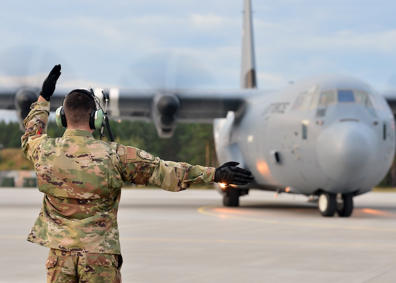 An Airman deployed with the 37th Airlift Squadron marshals a C-130J Super Hercules at Powidz Air Base, Poland, July 10, 2019. Approximately 80 Airmen and three aircraft deployed to Powidz Air Base in support of Aviation Rotation 19-3, a bilateral training exercise between the U.S. and Polish air forces. (U.S. Air Force photo by Staff Sgt. Jimmie D. Pike)