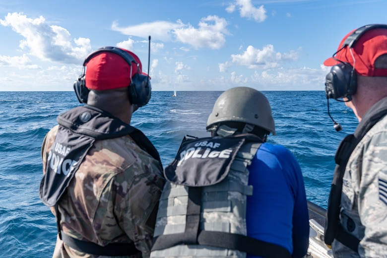 U.S. Air Force Tech. Sgt. Antonio J. Howard and Tech. Sgt. Randall D Perry, 6th Security Forces Squadron combat arms instructors, flank Senior Airman Bryan C. Scott, a 6th SFS marine patrolman, while he shoots an M240 machine gun at an orange target buoy 12 miles off the coast of St. Petersburg, Fla., July 2, 2019.