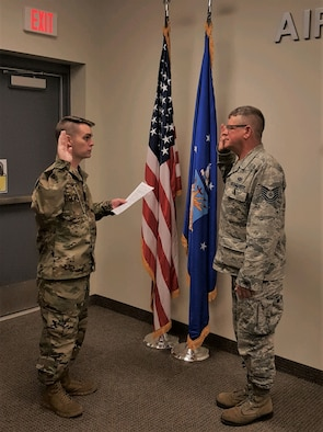 Maj. Ben Hulsey, 913th Force Support Squadron commander, facilitates the oath of enlistment to Tech. Sgt. Raymond Jauch, 96th Aerial Port Squadron air transportation specialist, on March 11, 2019 at Little Rock Air Force Base, Ark.  Jauch will retire this year with more that 28 years of active and reserve military service. (Courtesy photo)