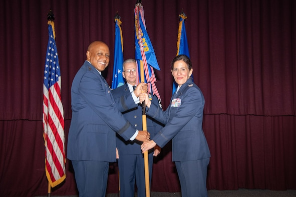 Lt. Gen. Anthony J. Cotton, Air University Commander and President, passes a guidon to Col. Kathryn A. Brown during her assumption of command for the Barnes Center July 11, 2019, at the Air Force Senior Noncommissioned Officer Academy Auditorium, Gunter Annex, Alabama. Brown received her commission in 1995 while attending Arizona State University. She served as the commander for the 11th Operations Group, Joint Base Andrews, Maryland, before assuming command of the center.