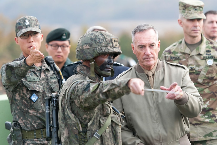 Soldier points out military features to general.