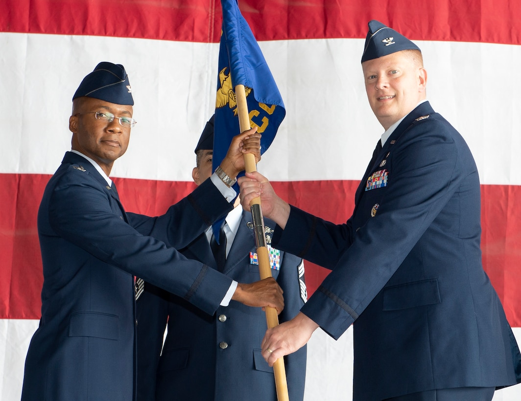 U.S. Air Force Col. Gavin Marks, 55th Wing commander, passes the guidon to U.S. Air Force Col. Steven Wieland, incoming 55th Communications Group commander, during the 55th CG Change of Command ceremony July 10, 2019, at Offutt Air Force Base, Nebraska. Wieland assumes command from U.S. Air Force Col. Corey Ramsby, who departs to be a ROTC commandant at the University of Notre Dame. (U.S. Air Force photo by L. Cunningham)