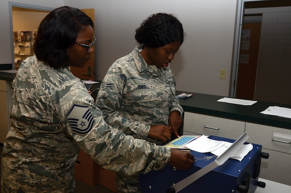 Master Sgt. Siearra Williams, 445th Force Support Squadron NCO in charge of customer support, teaches Airman 1st Class Tyra Davis, customer support assistant, how to use the dog tag machine June 20, 2019. Davis enters a service member's information that will be engraved into small metal plates