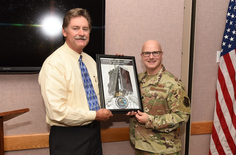 Mark Kostelic, Boeing Company, WGS sustainment program manager, hands over control of Wideband Global Satellite-10 to Lt. Col. Timothy Ryan, 4th Space Operations Squadron commander, during a ceremony at Schriever Air Force Base, Colorado, July 10, 2019.  WGS produces flexible, high-capacity communications for the joint warfighter through procurement and operation of the satellite constellation and the associated control systems. (U.S. Air Force Photo by Staff Sgt. Matthew Coleman-Foster)