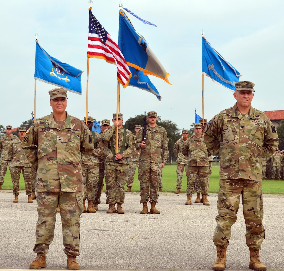 Col. Ingrid Parker (left), 470th Military Intelligence Brigade outgoing commander, and Col. Daniel Allen, 470th MI Brigade incoming commander, stand at attention during the brigade's change of command ceremony at the MacArthur Parade Field at Joint Base San Antonio-Fort Sam Houston July 9.