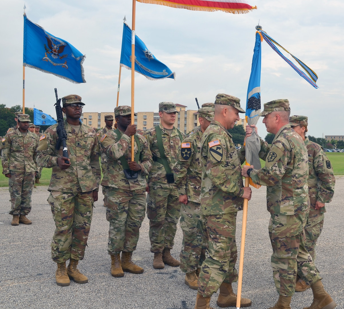 Col. Daniel Allen (left), 470th Military Intelligence Brigade incoming commander, accepts the brigade's guidon from Maj. Gen. Gary Johnston, U.S. Army Intelligence and Security Command commanding general (right), during the brigade's change of command ceremony at MacArthur Parade Field at Joint Base San Antonio-Fort Sam Houston July 9. Johnston was the presiding officer for the ceremony.