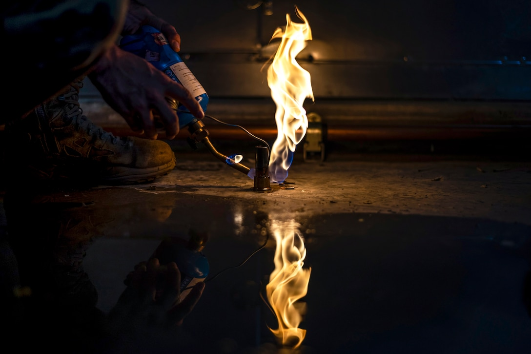 A soldering tool held by an airman creates a flame reflected in a puddle in an otherwise dark area.