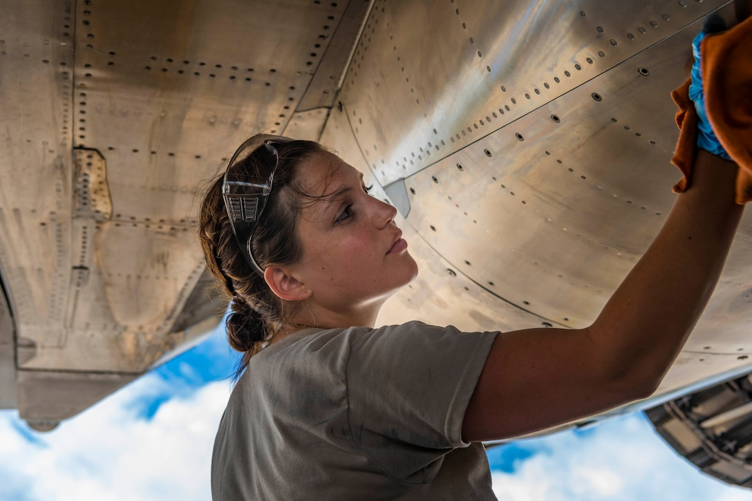 An airman uses a rag to clean the side of an aircraft.