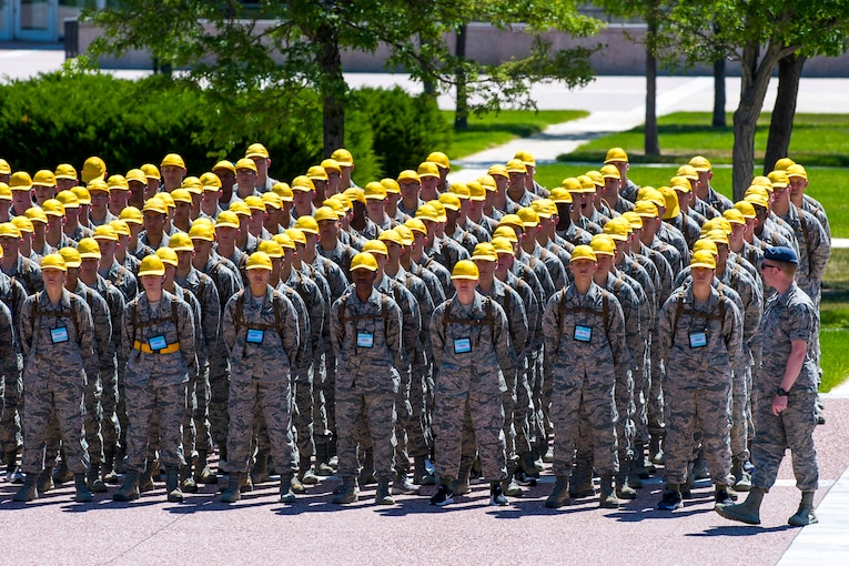A large group of cadets stand in formation wearing yellow hats.