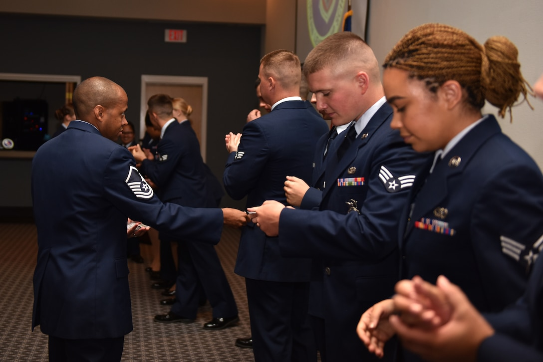U.S. Air Force Master Sgt. Sheraz Cedeno, 17th Training Wing Airman Leadership School commandant, coins and congratulates graduates of class 19-E after their graduation held at the event center on Goodfellow Air Force Base, Texas, July 11, 2019. Graduates from the leadership course will go on to become first-line supervisors at their workplaces, putting into practice the skills they learned in class. (U.S. Air Force photo by Senior Airman Seraiah Wolf/Released)
