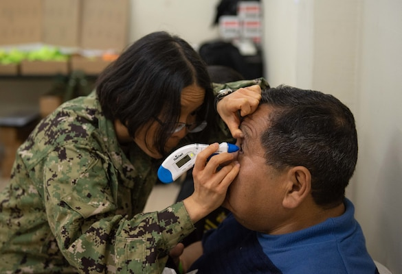 An optometrist examines a patient.