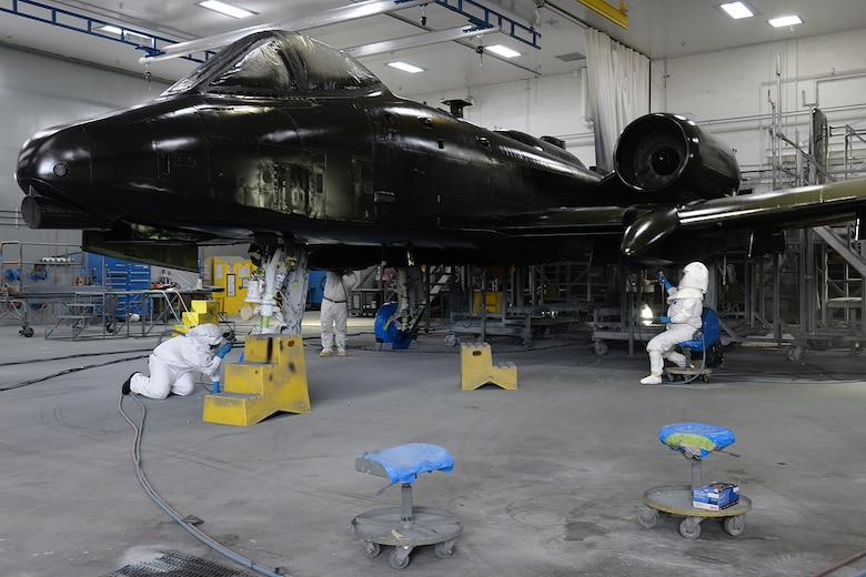 Corrosion control technicians apply primer to an A-10 Thunderbolt II