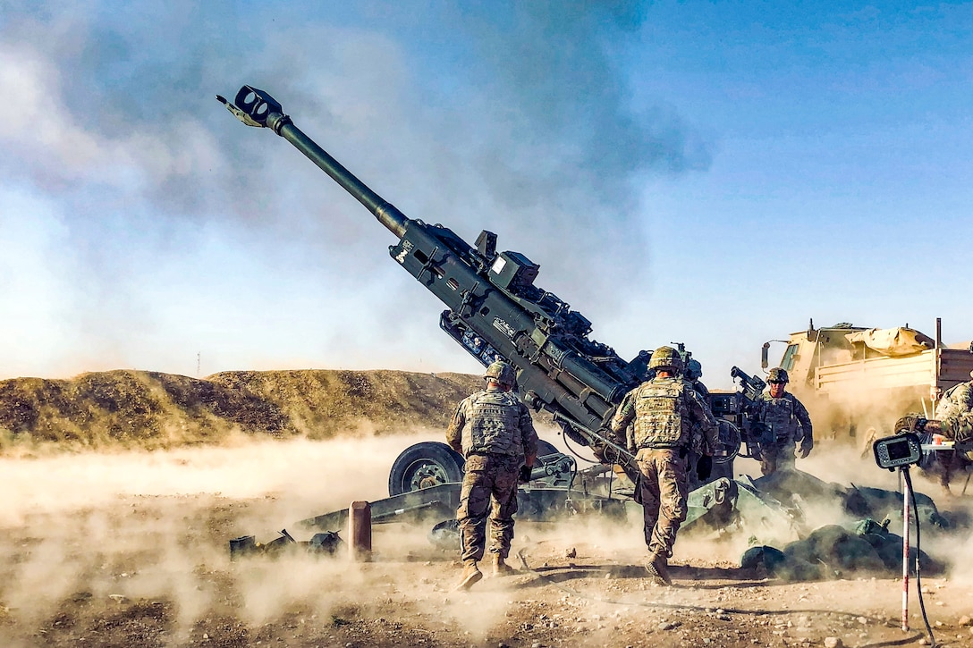 Soldiers fire a howitzer in a desert.