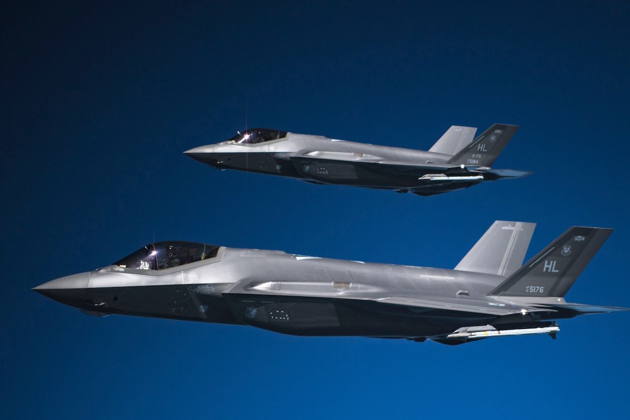 Two military jets fly in formation.