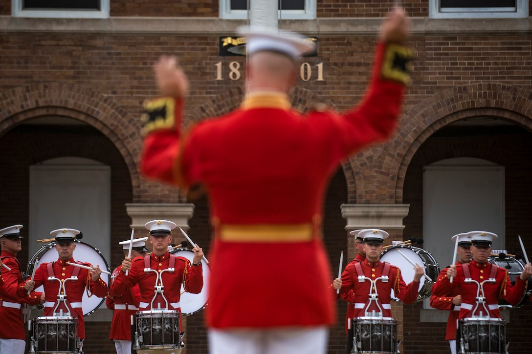 Marine Corps drummers stand in formation and perform as a conductor, shown from behind, leads them.