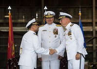 Incoming Naval Support Activity Lakehurst commander, U.S. Navy Capt. William Sherrod, accepts the responsibility of command from outgoing NSA Lakehurst commander, U.S. Navy Capt. Muhammed Khan, Joint Base McGuire-Dix-Lakehurst, New Jersey, July 12, 2019. Rear Adm. Charles Rock, commander of Navy Region Mid-Atlantic, presided over the ceremony.