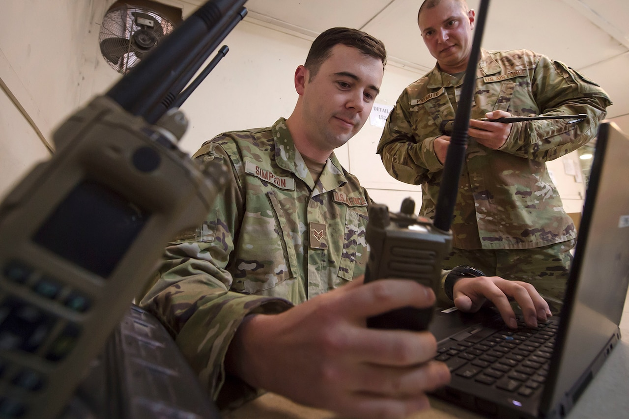 Airmen operate a radio and a laptop.