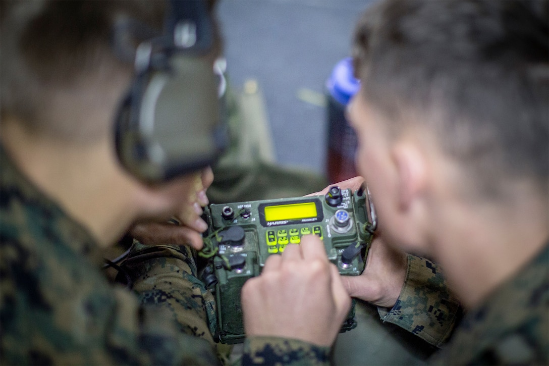 Marines type on a tactical radio keypad with a lighted display.