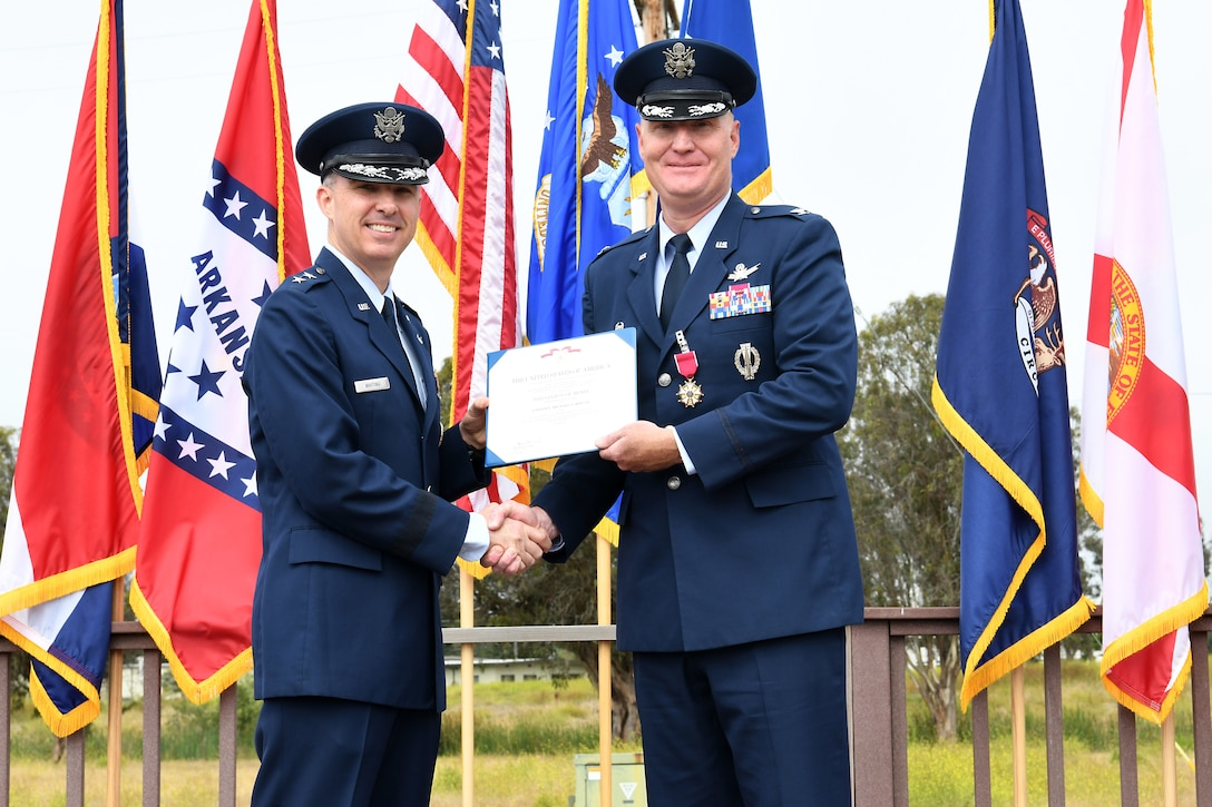 Maj. Gen. Stephen N. Whiting, 14th Air Force commander and Joint Force Space Component Command deputy commander, presents Col. Michael S. Hough, outgoing 30th Space Wing commander, with an award during a change of command ceremony July 12, 2019, at Vandenberg Air Force Base, Calif.