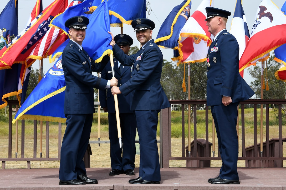 Maj. Gen. Stephen N. Whiting, 14th Air Force commander and Joint Force Space Component Command deputy commander, presents the 30th Space Wing guidon to the incoming 30th SW commander, Col. Anthony J. Mastalir, during a change of command ceremony July 12, 2019, at Vandenberg Air Force Base, Calif.