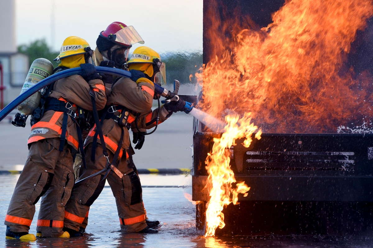 Airmen use a hose to spray a vehicle fire with water.