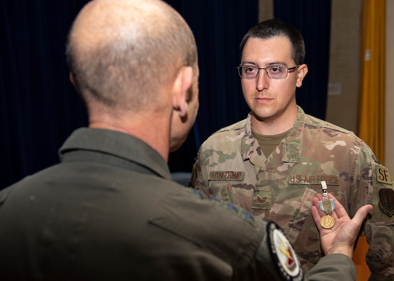 Gen. Mike Holmes places a medal on Staff Sgt. Kenneth Delongchamp.
