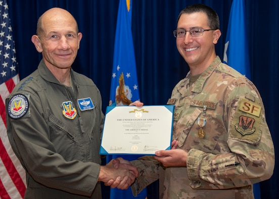 Gen. Mike Holmes and Staff Sgt. Kenneth Delongchamp pose for a photo.