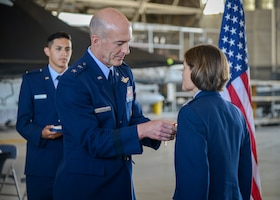 Maj. Gen. Christopher Azzano, Air Force Test Center Commander, places a Legion of Merit award on Col. Angela Suplisson, AFTC Vice Commander, during her retirement ceremony at Edwards Air Force Base, California, July 12. (U.S. Air Force photo by Giancarlo Casem)