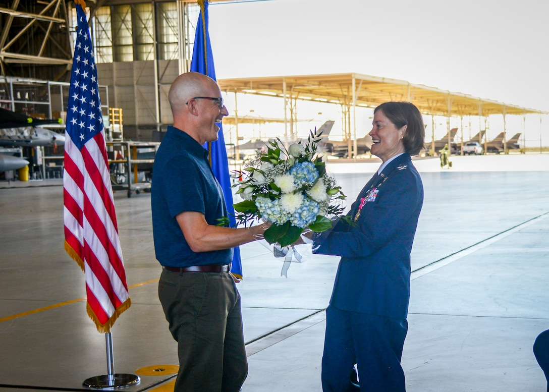 Fabrice Suplisson presents his wife, Col. Angela Suplisson, Air Force Test Center Vice Commander, a bouquet of flowers during her retirement ceremony at Edwards Air Force Base, California, July 12. Suplisson retired after 28 years of service. (U.S. Air Force photo by Giancarlo Casem