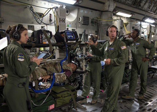 Airmen from Joint Base Charleston, S.C.'s 315th Aeromedical Evacuation Squadron prepare a mock patient during a drill in a C-17 Globemaster III, July 10, 2019. Drills performed while in-flight are meant to simulate real-life scenarios the 315th AES may encounter. (U.S. Air Force photo by Senior Airman William Brugge)