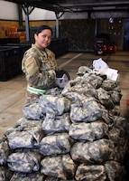 "Tech Sgt. Audrey Palacios, the 932nd Material Management Section non commissioned officer in charge, looks over bags in the supply line July 13, 2019 at Scott Air Force Base, Ill.  ""This helps pre-check equipment that will allow unit deployment managers to assist their people checking into the DCC (Deployment Control Center),"" said Palacios.  The inspection events started July 12 and continued through the July 13-14 Unit Training Assembly.   (U.S. Air Force photo by Lt. Col. Stan Paregien)"