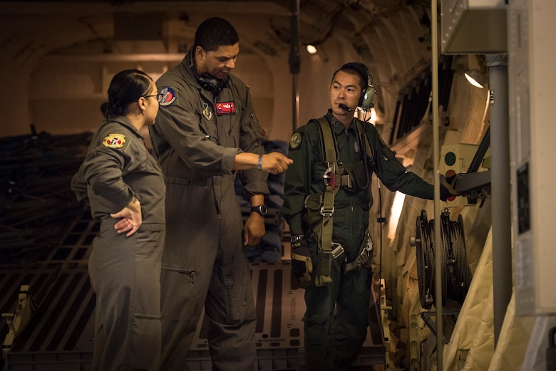 Master Sgt. Napoleon Ortiz, 374th Operations Support Squadron evaluator loadmaster, asks questions to a member of the Japan Air Self-Defense Force during a bilateral airlift exchange over Chubu region, Japan, July 10, 2019.