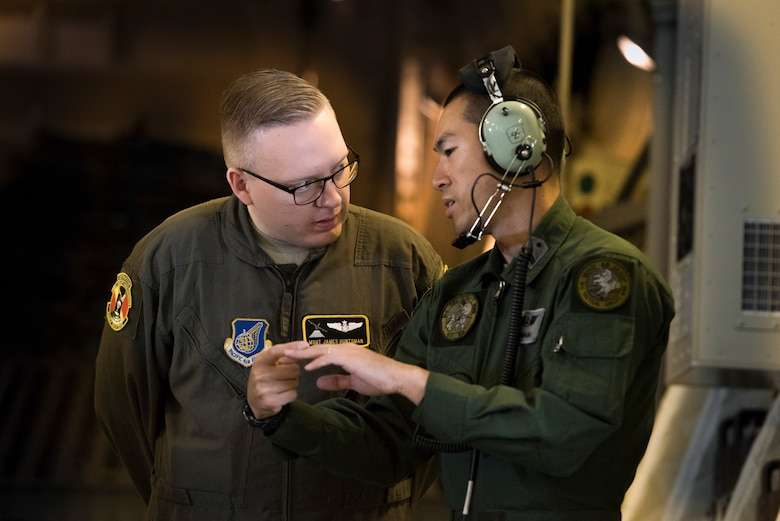 A member of the Japan Air Self-Defense Force answers questions from Master Sgt. James Huntsman, 36th Airlift Squadron flight chief and C-130J instructor loadmaster, during a bilateral airlift exchange over Chubu region, Japan, July 10, 2019.