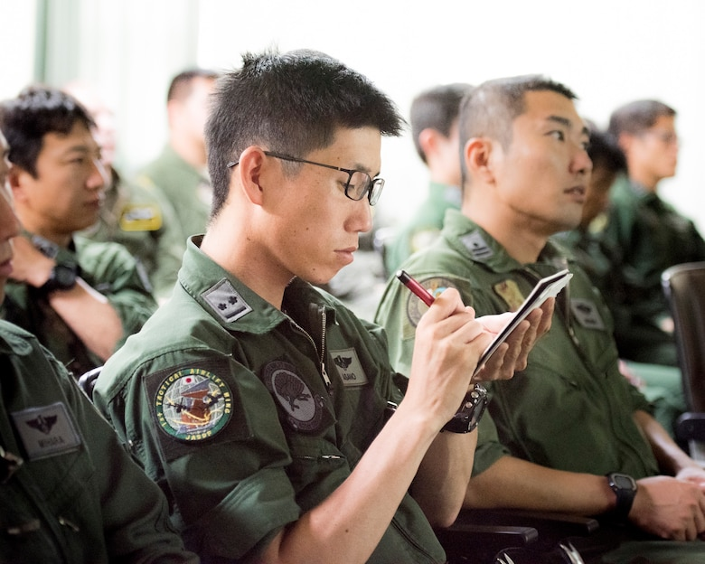 A member from the Japan Air Self-Defense Force makes a note during a briefing by members from 374th Airlift Wing at Iruma Air Base, Japan, July 10, 2019