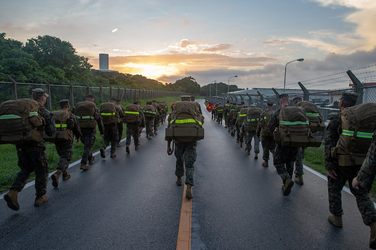 A group of Marines walk up a street at twilight.