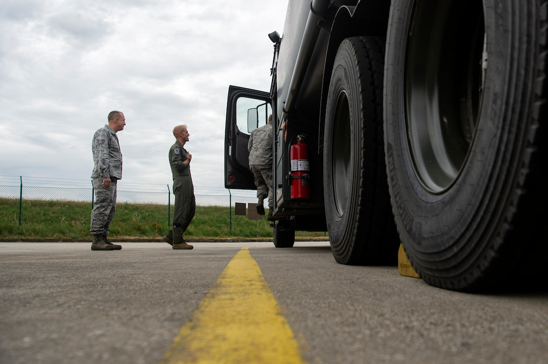 U.S. Air Force Maj. Michael Slotten, 421st Fighter Squadron F-35A Lightning II pilot, center, Tech. Sgt. Charles Moore, 52nd Logistics Readiness Squadron fuels distribution NCO in charge, left, and Staff Sgt. Jonathan Knepler, 52nd LRS preventive maintenance team NCO in charge, right, check out a fuels truck at Spangdahlem Air Base, Germany, July 11, 2019. Slotten was stationed at Spangdahlem from 2004 to 2006 as an Airman first class fuels distributor operator. He visited his old unit and became requalified to refuel aircraft. (U.S. Air Force photo by Airman 1st Class Valerie Seelye)