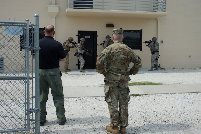 U.S. Army Command Sgt. Maj. John W. Troxell, senior enlisted advisor to the chairman of the Joint Chiefs of Staff, observes a door breach demonstration by members of the 6th Security Forces Squadron, during a MacDill Air Force Base visit, July 11, 2019. During visits to Joint Operational Areas, posts and bases with service members from different branches, the SEAC identifies issues that affect service members, and works to integrate solutions to increase readiness, effectiveness, health, and welfare of the total force. (U.S. Air Force photo by Airman 1st Class Shannon Bowman)