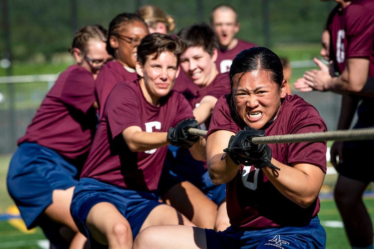 Air Force basic cadets in burgundy t-shirts and blue shorts pull a rope during tug of war outside.