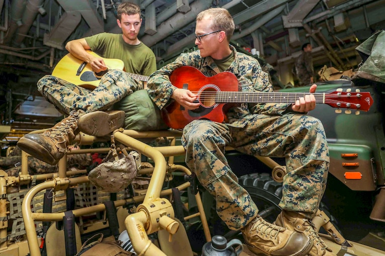 Two Marines sit on structural bars atop an open vehicle and play guitar.