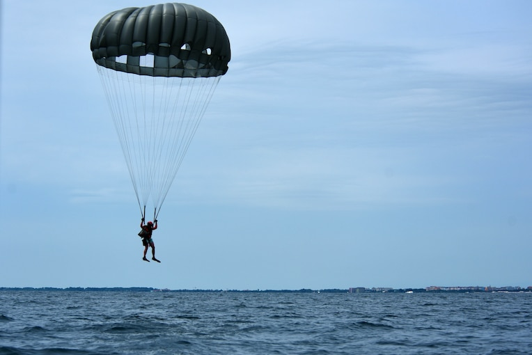 An airman wearing a parachutes descends into water.