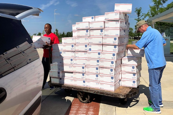 U.S. Army Sgt. Maj. Ronald Houston, U.S. Army Financial Management Command operations, left, and Mark Sullivan, USAFMCOM financial management systems analyst, right, load care packages into a van outside the Maj. Gen. Emmett J. Bean Federal Center, Indianapolis, June 29, 2019. USAFMCOM, Defense Finance and Accounting Service and Army Human Resources Command Soldiers and civilian employees volunteered their off-duty time to package and help ship more than 200 care packages to financial management service members currently deployed in Southwest Asia. (U.S. Army courtesy photo provided by Mark Sullivan, U.S. Army Financial Management Command)