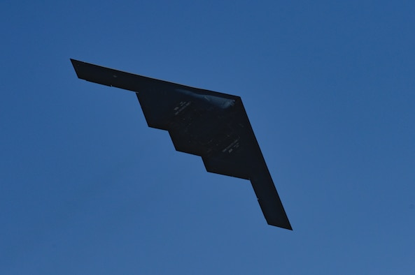 A B-2 Spirit is seen in silhouette from below as it performs a low flyover during the 2019 Wings Over Whiteman Air & Space Show at Whiteman Air Force Base, Missouri, June 15, 2019. The B-2 fleet is operated by the 509th Bomb Wing. During the air show, pyrotechnics simulated notional explosives for spectators on the ground. (U.S. Air Force photo by Tech. Sgt. Alexander W. Riedel)