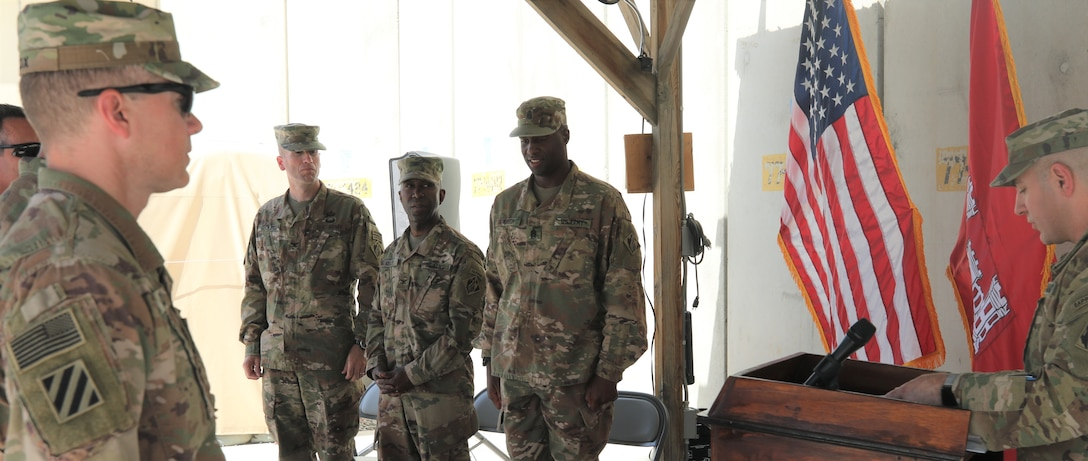 District team members honor the changing of the leadership as Lt. Col. Mike Harding reads the orders announcing Col. Chris Becking as the Commanding Officer of the Afghanistan District, assuming command from Col. Jason Kelly.