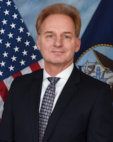 Thomas B. Modly poses for an official portrait against a blue background with the U.S. and Navy flags.