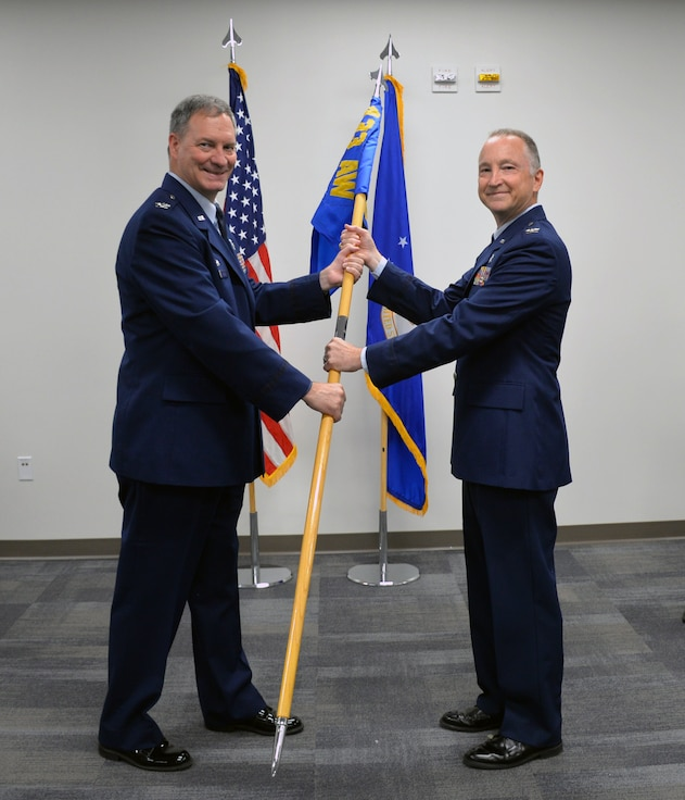 Col. Terry W. McClain, 433rd Airlift Wing commander, passes the 433rd Medical Group guidon to Col. Michael C. Brice to signify the assumption of command during a ceremony July 13, 2019 at Joint Base San Antonio-Lackland, Texas.