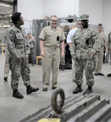 EMC AnnMarie Allison (left) and EM1 Jasmin McDowell explain to Rear Adm. Tom Anderson (center) the Intermediate Level maintenance capabilities of the Outside Machine Shop at Southeast Regional Maintenance Center.