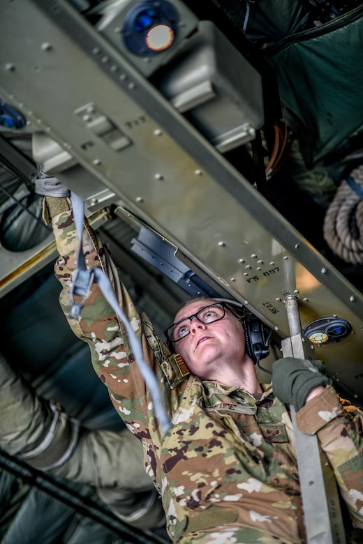A Reserve Citizen Airman with the 445th Aeromedical Evacuation Squadron reaches up to connect cargo straps aboard a Youngstown Air Reserve Station C-130H Hercules aircraft on July 10, 2019, on the flightline at Wright-Patterson Air Force Base.