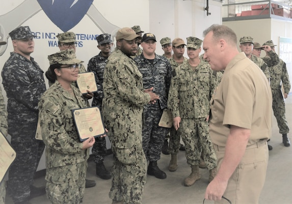 Rear Adm. Tom Anderson (right) congratulates GSM1 Maria Santana for her recently completed NAMTS qualification.