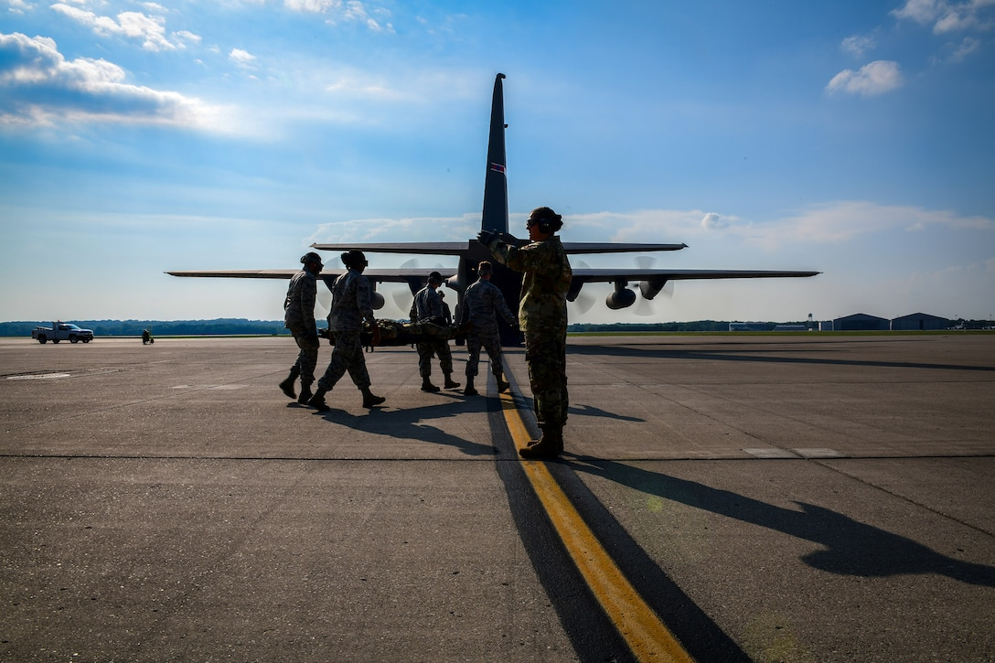Reserve Citizen Airmen with the 445th Aeromedical Evacuation Squadron walk toward a Youngstown Air Reserve Station C-130H Hercules on July 10, 2019, on the flightline at Wright-Patterson Air Force Base.